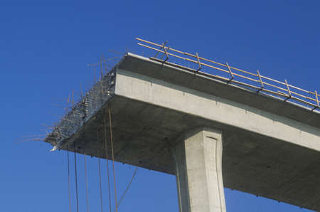 continued: A concrete freeway structure ends abruptly with iron support structures sticking out and safety rails lining the top edge until further construction is continued, USA