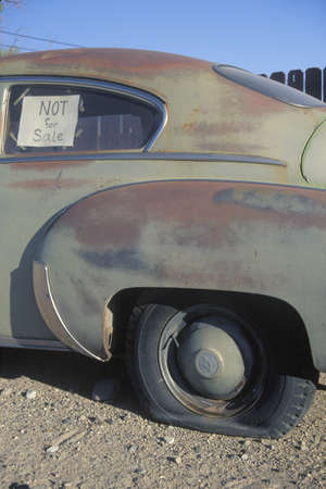 junked: An old car with a flat tire has a not for sale sign in its window Editorial