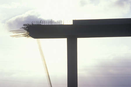 A concrete freeway structure ending abruptly with iron support structures sticking out until further construction is continued, USA