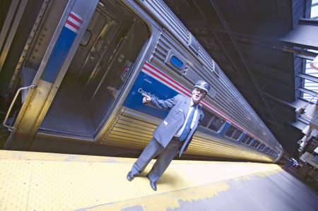 """""""Angled view of conductor at Amtrak train platform announces """"""""All Aboard"""""""" at East Coast train station on the way to New York City, New York, Manhattan, New York"""""""