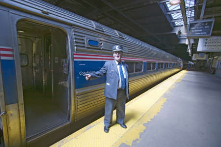 aboard: Conductor at Amtrak train platform announces All Aboard at East Coast train station on the way to New York City, New York, Manhattan, New York