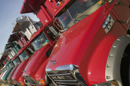 mack: Bright red Mack dump trucks line the road in a row, in Maine near the New Hampshire border