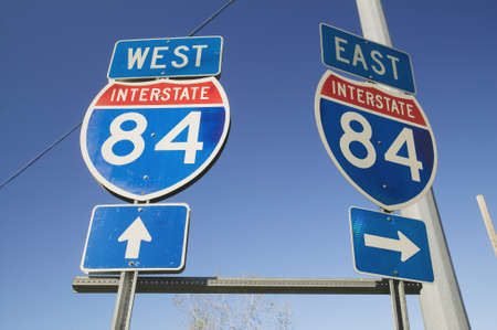 cultural artifacts: Interstate highway signs for East and West on Interstate Highway 84 Editorial