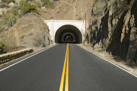 Double yellow-line leads to a tunnel through a mountain on highway 33 in Ojai, Ventura County California