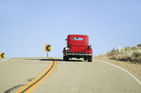 A restored bright Red Roadster hotrod pickup truck, mid-30s, drives rural highway in Kern County near Lockwood Valley, CA