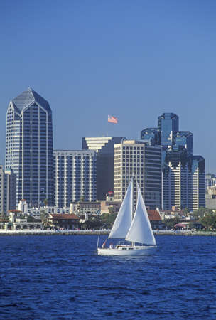 harbors: Sailboat sails in view of the San Diego skyline as seen from Coronado, San Diego, California