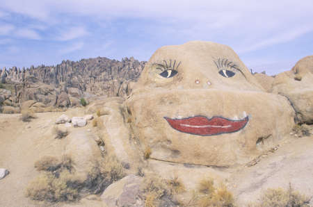 defaced: Red lips and womans face painted on rock in Alabama Hills, California