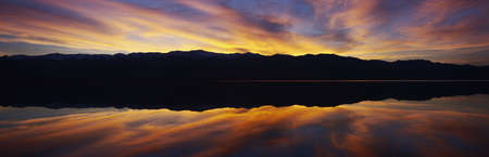 Panoramic view at sunset of flooded salt flats and Panamint Range Mountains in Death Valley National Park, California