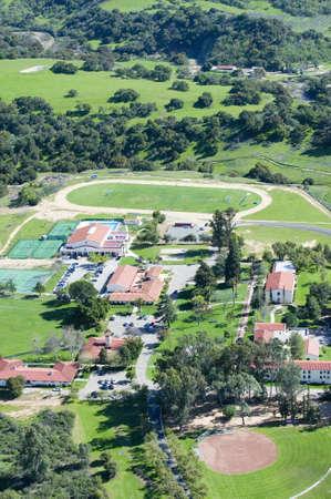 Springtime aerial view of Villanova Prep school with track, pool, baseball diamond, tennis courts and campus in view, Ojai, CA