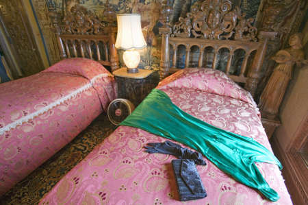 Interior of guest bedroom with displayed antique clothing of the day at Hearst Castle, Americas Castle, San Simeon, Central California Coast