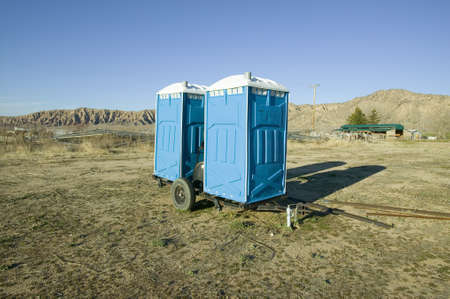 Two out houses, mobile blue bathrooms, sit on trailer in the middle of a field in Ventura County, California off of highway 33 near Cuyama