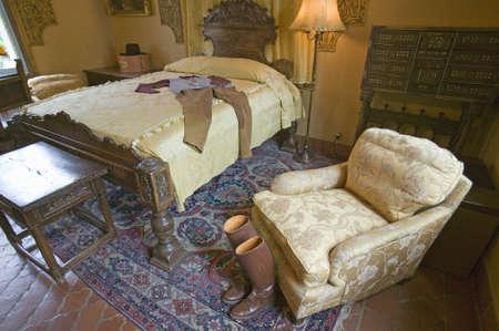 guest room: Stivali da equitazione e vestito visualizzati in camera per gli ospiti di Hearst Castle, San Simeon, California Editoriali