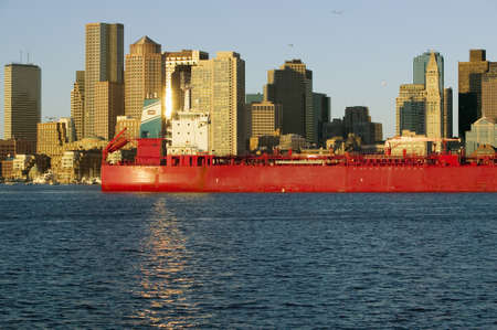 charles county: Bright red cargo ship travels in front of Boston Harbor and the Boston skyline at sunrise as seen from South Boston, Massachusetts, New England Editorial