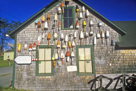 Lobster buoys on side of building in Muscongus Bay in New Harbor ME