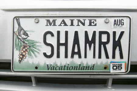 A Maine license plate reads, SHMRK