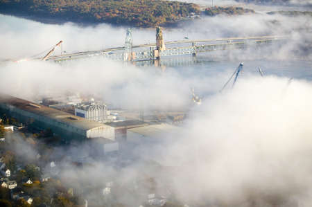 aegis: Aerial view of fog over Bath Iron Works and Kennebec River in Maine.  Bath Iron Works is a leader in surface combatant design and construction with a $27 million dollar contract from the Navy for maintenance, repair and upgrades to Aegis destroyers.
