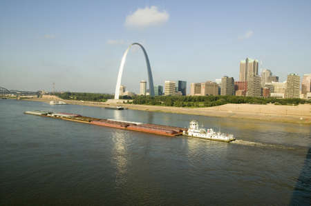 Daytime view of tug boat pushing barge down Mississippi River in front of Gateway Arch and skyline of St. Louis, Missouri as seen from East St. Louis, Illinois on the Mississippi River