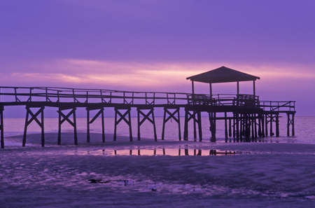 ms: Sunrise over the Gulf of Mexico with pier in Biloxi, MS Editorial