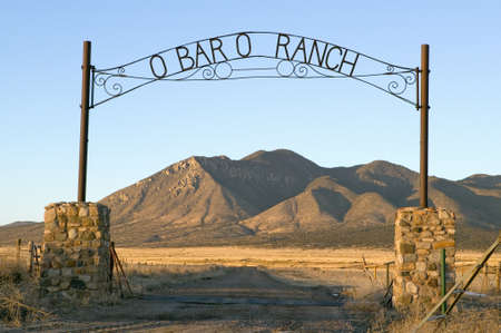 entrance gate: OBaro Ranch gate and mountains at sunset in central New Mexico, Route 48 near Smokey Bear Historical Park Editorial