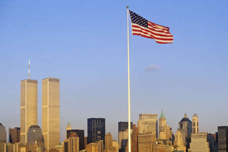 American Flag flying over skyline of New York City from New York Harbor, NY