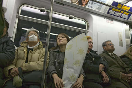 Woman on New York Subway system with mask over her face to prevent disease, New York