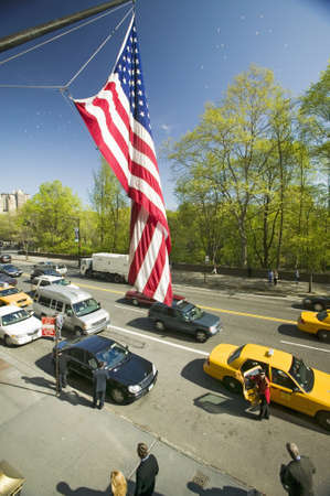 American Flag flies over Central Park in spring with yellow taxies in front of Helmsely Park Lane, Manhattan, New York City, NY