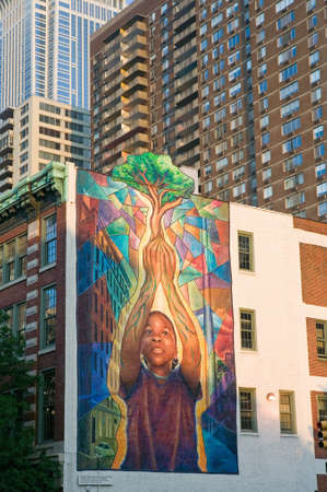 wall mural: Wall mural of child holding tree in Philadelphia, Pennsylvania