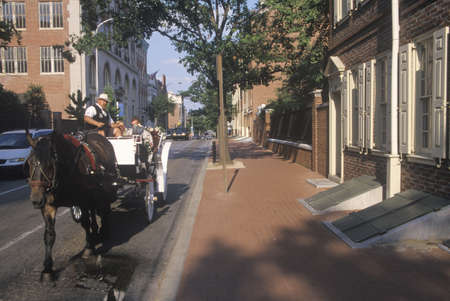 brotherly love: Horse and carriage riding in historic district of old Philadelphia, PA, home of Ben Franklin and Declaration of Independence and US Constitution