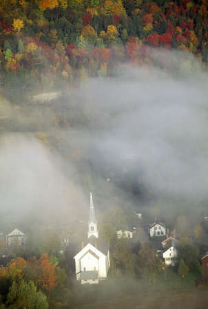 Aerial view of church steeple wreathed in morning fog in autumn, Waitsfield, VT