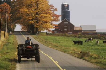 Tractor on farm road with barn and silo in background in autumn, VT