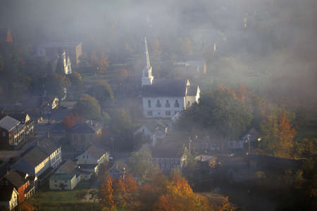 Aerial view of Waitsfield, VT in fog with church steeple on Scenic Route 100 in Autumn