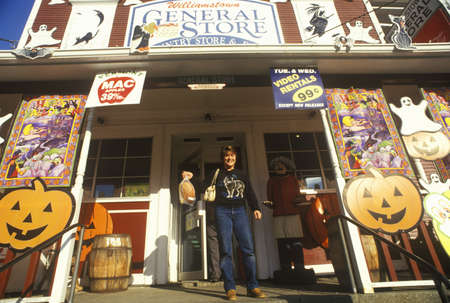 country store: Man on porch of Country Store in Williamstown, VT covered with Halloween decorations Editorial