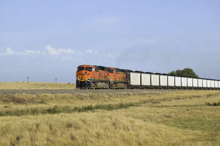 Red freight train traveling through western Nebraska carrying coal