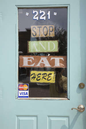 Sign on the door of Aunt B restaurant that reads Stop and Eat Here in Walnut, Iowa Editorial