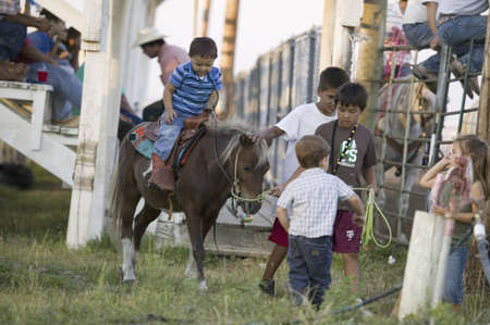 sioux: Little cowboys riding pony at PRCA Rodeo at Lower Brule, Lyman County, Lower Brule Sioux Tribal Reservation, South Dakota, 58 miles Southeast of Pierre near Missouri River, August 10, 2007 Editorial