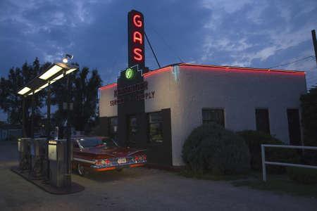 gasolinera: Muestra de ne?e gasolina y 1960 Chevrolet Impala rojo lectura en Kensinger Service & Supply gasolinera hist?o, en EE.UU. la autopista 30, la carretera de Lincoln, Grand Island, Nebraska Editorial