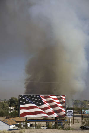 az: Brush fire in desert emitting large black plumes of smoke behind large billboard of American Flag, east of Needles in Arizona Editorial