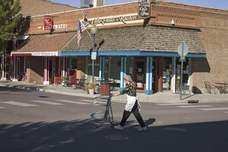 everyday scenes: Donna con carrello della spesa che attraversa Main Street di Palisade Colorado, a est di Grand Junction