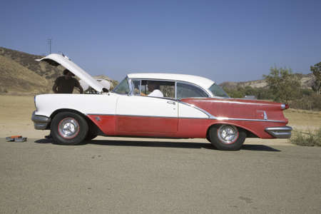 1954 red & white Oldsmobile with hood up and two males stranded after breakdown, near Santa Paula, California, off Highway 126