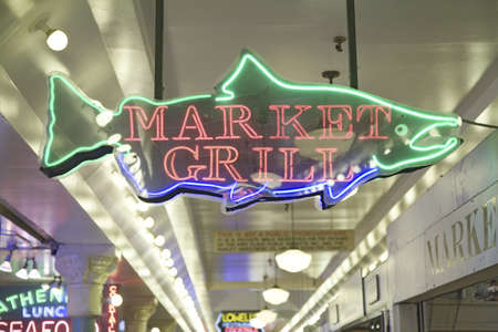 Pike Place Fish Market, in downtown Seattle, Washington displaying Market Grill neon sign in interior view of the fish market
