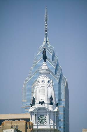 Statue of William Penn on the top of the renovated City Hall and a modern office building behind it in Philadelphia, Pennsylvania