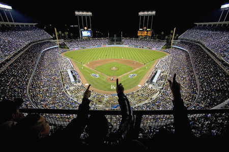 ca: Silhouette of Dodger fans cheer and point from grandstands overlooking home plate at National League Championship Series (NLCS), Dodger Stadium, Los Angeles, CA on October 12, 2008