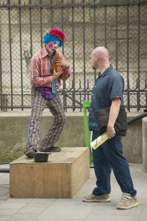 Pedestrian and street mime clown across from the Notre Dame Cathedral, Paris, France