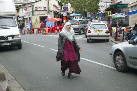 femme musulmane: Femme musulmane marchant dans la rue, Paris, France