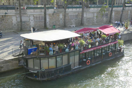 sightseers: Boat with restaurant docked on Seine River, Paris, France