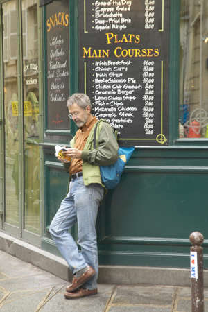 Man reading in front of cafe, Paris, France
