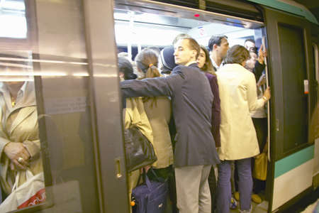 People crowding into metro train at rush hour, Paris, France