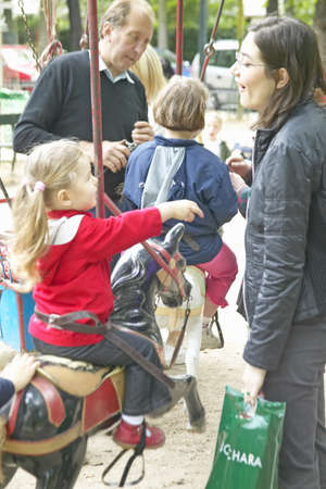 Parents and children at carousel ride in park, Paris, France