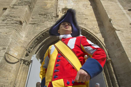 Costumed guard greeting people in front of Palace of the Popes, Avignon, France