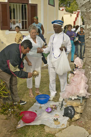 San Lazaro Catholic Church with Santeria priest offering services in El Rincon, Cuba Publikacyjne